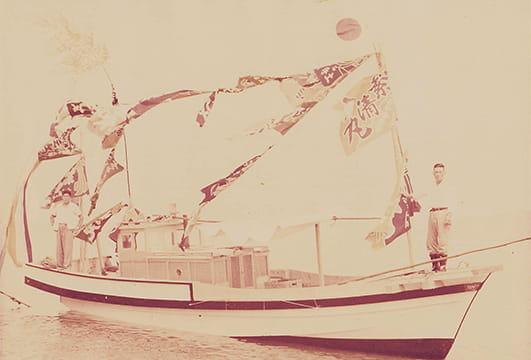 大漁旗を掲げ、航行する初代繁清丸
