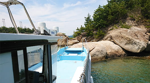 岩場に船首を近づけている作業船イーグル